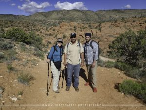 three people standing on trailhead